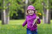 Girl in pink with bouquet, jumping on the green grass. — Stock Photo