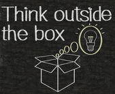 Thinking outside the box written on blackboard background — Stockfoto