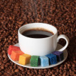 Stock Photo: Smoking cup of coffee with colorful sugar, on coffee beans background