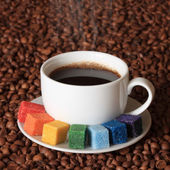 Smoking cup of coffee with colorful sugar, on coffee beans background — 图库照片
