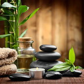 Zen basalt stones and spa oil on the wood — Stock Photo