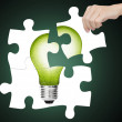 Hand completing jigsaw puzzle of green energy light bulb, sign of environment saving — Stock Photo #42848661