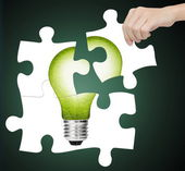 Hand completing jigsaw puzzle of green energy light bulb, sign of environment saving — Stock Photo