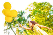 Happy girl with yellow balloons — Stock Photo