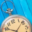 Close up of old style pocket watch on blue wooden backround — Stock Photo #40308173