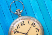 Close up of old style pocket watch on blue wooden backround — Stock Photo