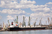 Large cargo ship in a dock at port. Cloudy sky — Foto de Stock