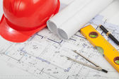 Red helmet, construction drafts and tools on the table — Stock Photo