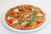 Pizza with tomato and arugula on white plate — Stock Photo