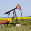 Oil pump with sunflowers field on the background — Stock Photo