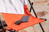 E-reader, smart phone and sunglasses on beach chair (on vacation) — Stock Photo
