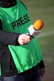 Hand hold microphone for interview during a football mach — Stock Photo