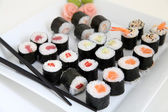 Sushi set on white plate. Traditional japanese sushi rolls — Stock Photo