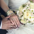 Bride and groom's hands with wedding rings and bouquet of flowers — Stock Photo