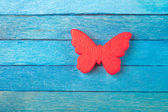 Decorative red butterfly on blue wooden background — Stock Photo