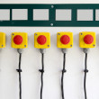Red big buttons on the wall, with cables — Stock Photo