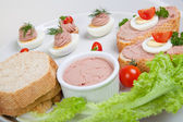 Plate with slices of bread with home made pate, decorated with vegetables — Stock Photo