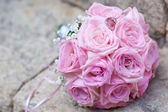 Silver wedding rings on wedding bouquet of pink roses — Stock Photo