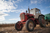 Old tractor in field, cloudy sky — Stock Photo