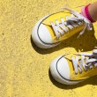 Yellow sneakers on yellow background — Stock Photo