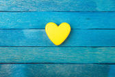 Decorative yellow heart on blue wooden background — Stock Photo