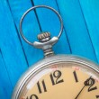 Close up of old style pocket watch on blue wooden backround — Stock Photo #44348425