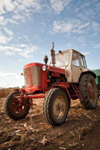 Old tractor in field, against a cloudy sky — Stock Photo