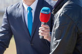 News journalist with microphone interviewing — Stock Photo