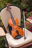 Violin and bow on a chair in the garden — Stock Photo