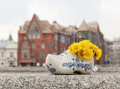 Dutch clogs with yellow flower — Stock Photo