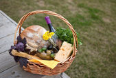 Food and wine in the wicker basket — Stock Photo