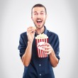 Young happy man watching movie and holding popcorn — Stock Photo #40011787