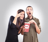 Young couple watching a movie and eating popcorn — Stock Photo