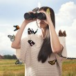 Young woman watching with binocular with butterflies — Stock Photo #40035221