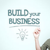 "Man writing ""build your business"" — Stock Photo"