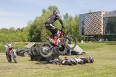 Jump with bycicle over people during celebration of Gauja day. — Stock Photo
