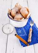 Sugar powdered cinnamon doughnuts in a metal rustic bowl on white wooden background with sieve and fork close up — Stock Photo