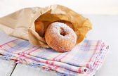 Sugar powdered cinnamon doughnuts in paper bag on white wooden background — Stock Photo