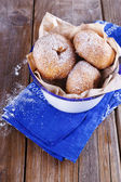 Sugar powdered cinnamon doughnuts in a metal rustic bowl on rustic wooden background — Stock Photo