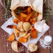 Healthy vegetable chips on paper with sea salt, rosemary and garlic — Stock Photo #44302481