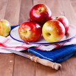 Red organic apples in a metal plate on wooden background — Stock Photo