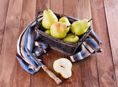 Organic pears in a woven basket on wooden background — Stock Photo
