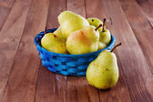 Organic pears in a blue woven basket on wooden background — Stock Photo