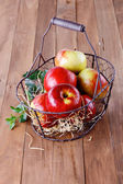 Red organic apples in a metal basket on wooden background — Stock Photo