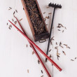 Black wild rice in a wooden box with chopsticks on a white wooden background — Stock Photo #44633343