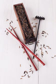 Black wild rice in a wooden box with chopsticks on a white wooden background — Stock Photo