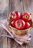 Red organic apples in a straw basket on wooden background — Stock Photo