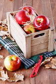 Red organic apples in a wooden crate on wooden background — Stock Photo