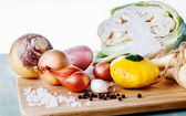 Organic vegetables on chopping board on wooden background — Stock Photo
