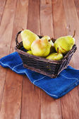 Pears in a woven basket on wooden background — Stock Photo